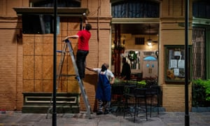 General Manager of Pere Antoine Restaurant Gaige Rodriguez, left, and cook Michael Dillon board up windows as they prepare for the arrival of tropical storm Zeta in New Orleans.