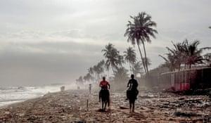 Abidjan, Ivory Coast: people ride horses on a beach