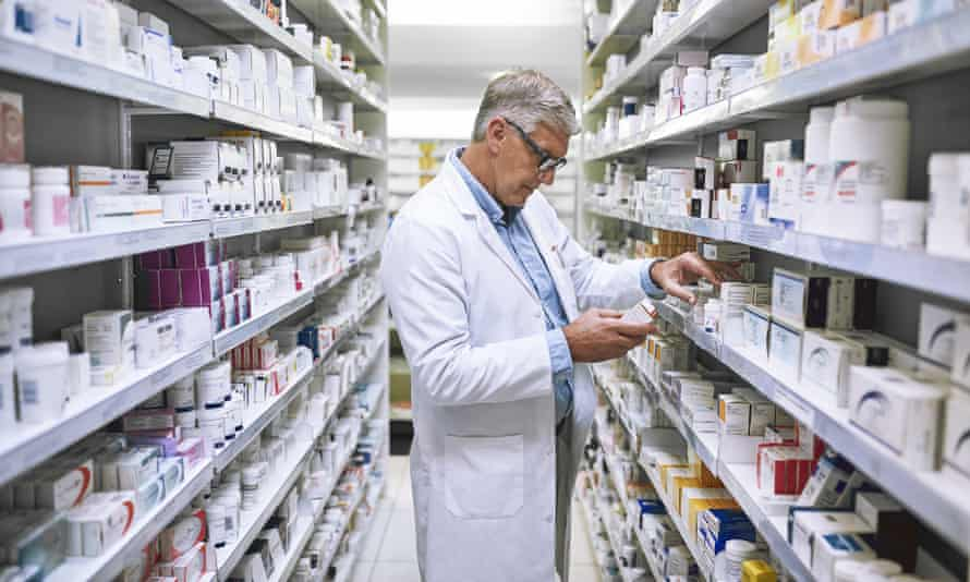 A pharmacist making notes of the medication stock on the shelves in a pharmacy.