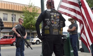 """""""We are not counter-protesters, we're just going to make sure Coeur d'Alene is safe,"""" said Conrad Nelsen of Coeur d'Alene, Idaho, as he holds a flag while standing next to armed citizen Dan Carson, left, during a protest on Tuesday."""