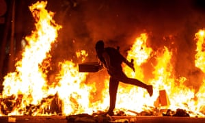 A protester runs accross the street in front of a burning barricade during a rally in downtown Barcelona on Tuesday night.