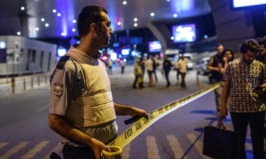 A policeman sets up a security perimeter as people leave the airport.