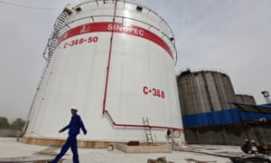 An employee walks past oil tanks at a Sinopec refinery in Wuhan, Hubei province, China.