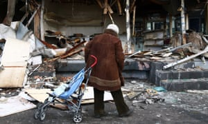 A woman with a pushchair examines the remains of a shop near an entrace to Sokol metro station