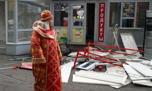A shop tout in period costume walks past partly demolished shops near the entrance to Sokol metro station