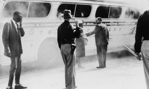 Police guard a burning bus in Anniston, Alabama, in May 1961, after a mob of white supremacists attacked it. On board were 'Freedom Riders'.