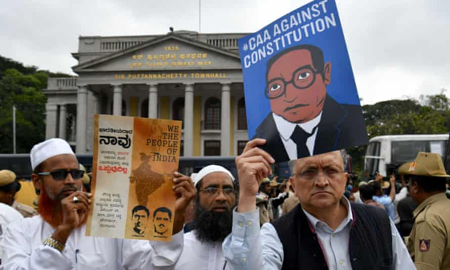 Historian Ramchandra Guha (R) holds a placard against India's new citizenship law.