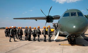 National Force military firefighters stand in line to board a plane to help fight fires in the Amazon
