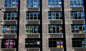Some of the designs from the 'Post-it war' are seen in the windows of an office block on Varick Street in lower Manhattan.