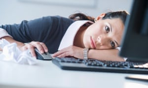 Businesswoman in front of computer, slumped on the desk looking tired.