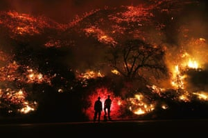 Firefighters monitor a section of the Thomas Fire along the 101 freeway north of Ventura, California