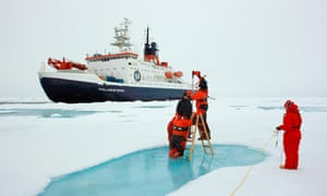scientists bore into arctic sea ice, the polarstern behind them