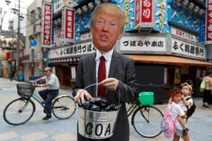 A protester wearing a Trump mask carries a 'coal' bucket while demanding that Japan stop supporting the fossil fuel industry