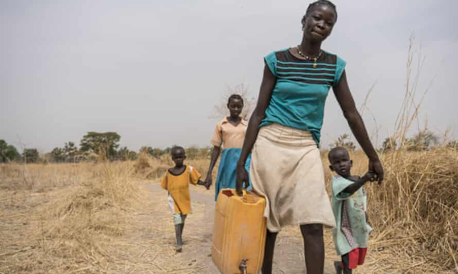 Abuk walks home after collecting clean water from a water point 4km away from her home.
