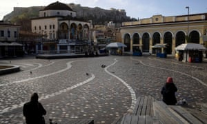 People sit on Monastiraki square in Athens after the Greek government imposed stricter lockdown measures.