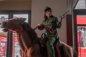 Woman in Red Army uniform on a stuffed horse