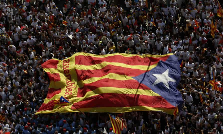 People in Barcelona with a giant <em>estelada</em> flag during a demonstration calling for the independence of Catalonia from Spain. But most people who speak Catalan also speak Spanish.