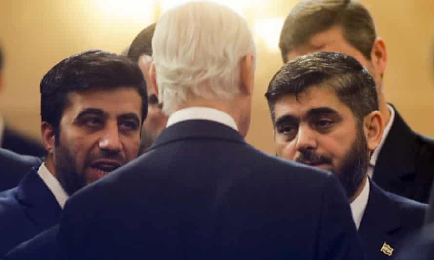 UN special envoy Staffan de Mistura (back to camera) speaks to the head of the Syrian opposition delegation Mohammed Alloush (right) before the talks