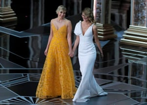 Presenters Greta Gerwig and Laura Dern walk onto the stage