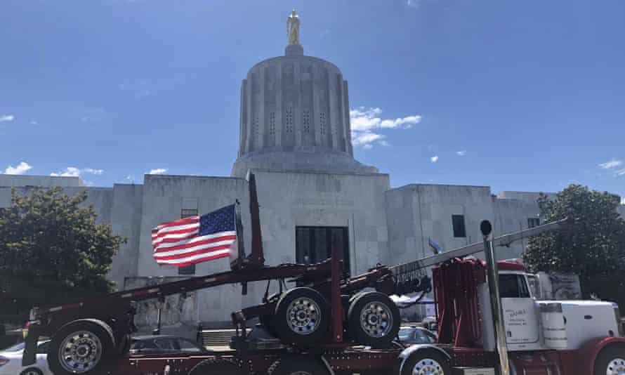 A truck moves around the Oregon state capitol in Salem on 12 June during a protest against climate bills that truckers say will put them out of business.