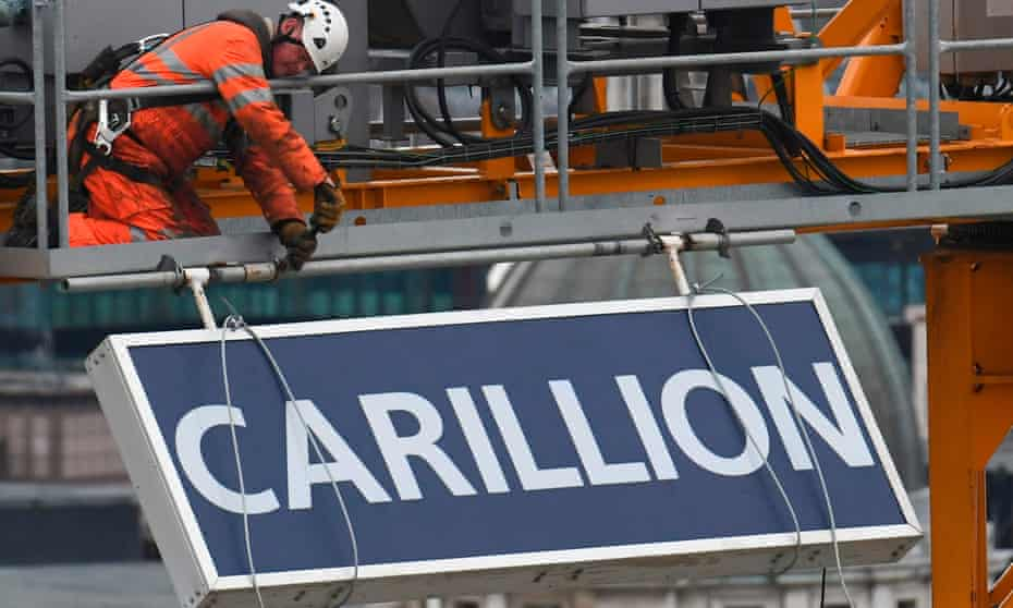 A worker takes down a sign showing the name of Carillion