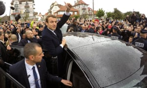 Emmanuel Macron greets supporters as he leaves a polling station in Le Touquet.