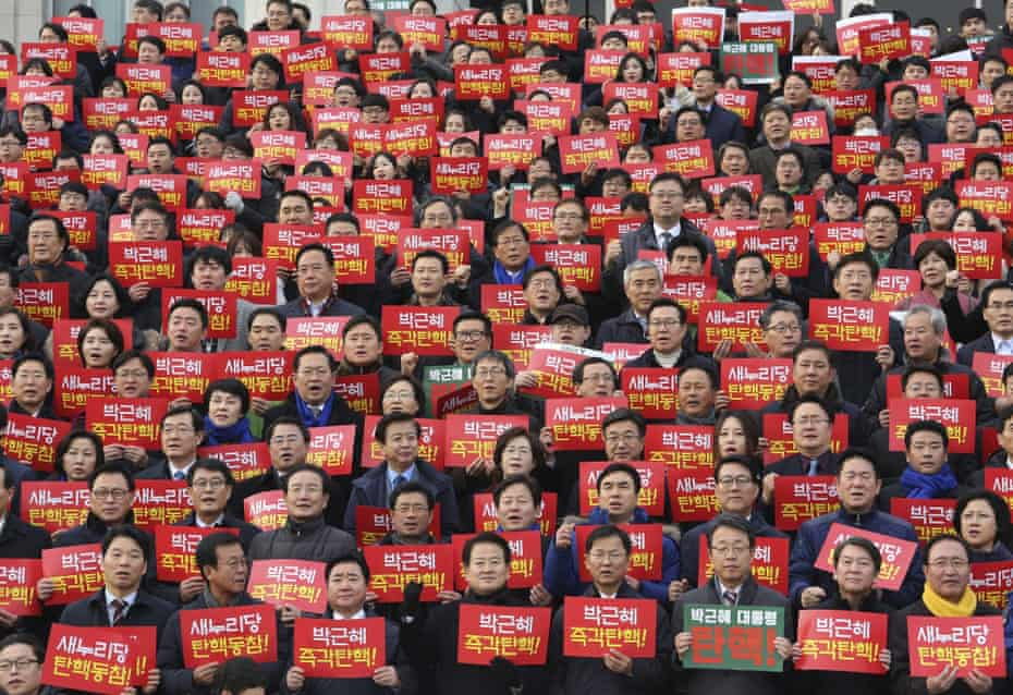 South Korean lawmakers and opposition party members hold placards demanding the impeachment of Park Geun-hye in December 2016.