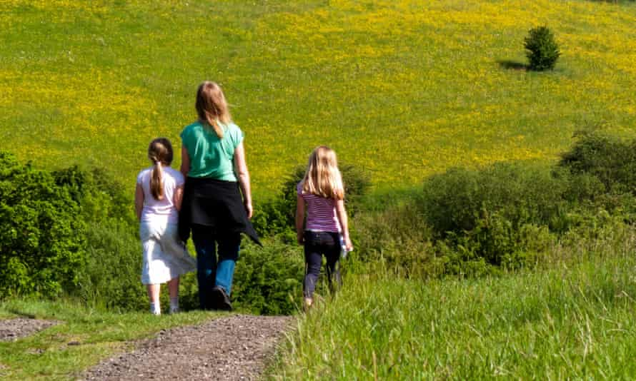 Woman and two young children walking down a country lane