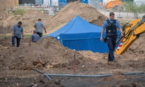 A policeman walks past a blue tent covering a British bomb found during construction works in Frankfurt.