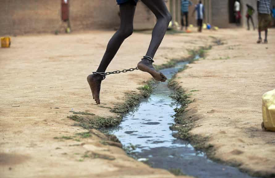 An inmate with shackles around his ankles skips over an open trench at Rumbek's central prison in South Sudan