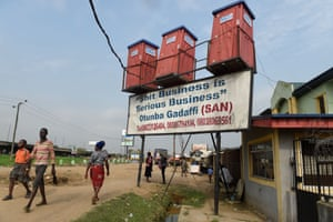 "People walk past mobile toilets for sale displayed along the road with a placard reading ""shit business is serious business"" at Kara-Isheri in Ogun State, southwest Nigeria."