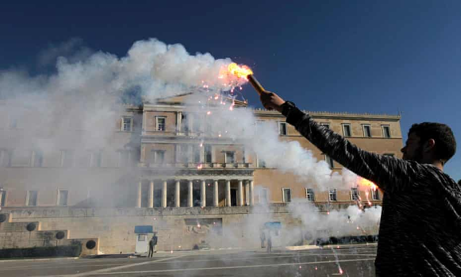 A student holds a flare in front of the parliament during an anti-austerity protest in Athens, Greece.