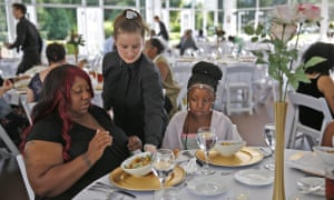 Katelin Decraene, center, gives Trishell Crawford and her daughter Jacqueline Crawford salads at a reception at the Ritz Charles, on Saturday, 15 July, 2017. Sarah Cummins called off her wedding and invited area homeless to enjoy the reception.