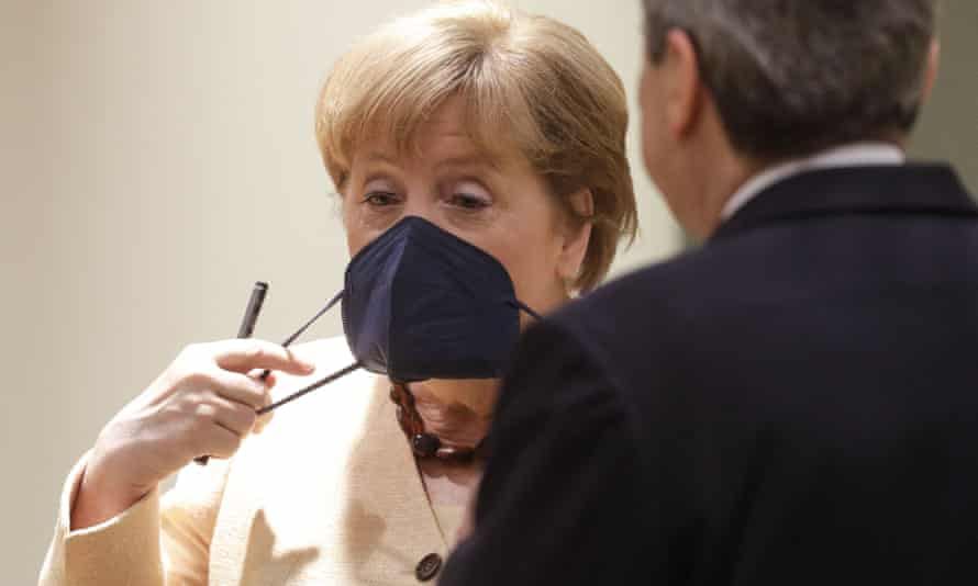 Angela Merkel adjusts her mask on the second day of the EU summit
