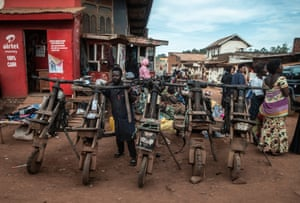 "Those who can't afford motorcycles transport cargo on wooden ""Chukudus"" in the busy street markets of Butembo"