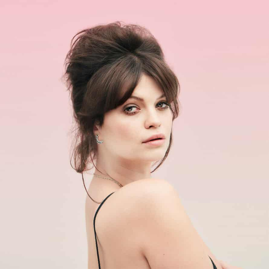 Pixie Geldof , dark hair gathered on top of her head, looking sideways to the camera, a black strap on her bare shoulder