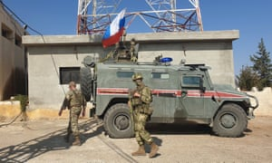 Soldiers with a Russian military police vehicle in Kobane