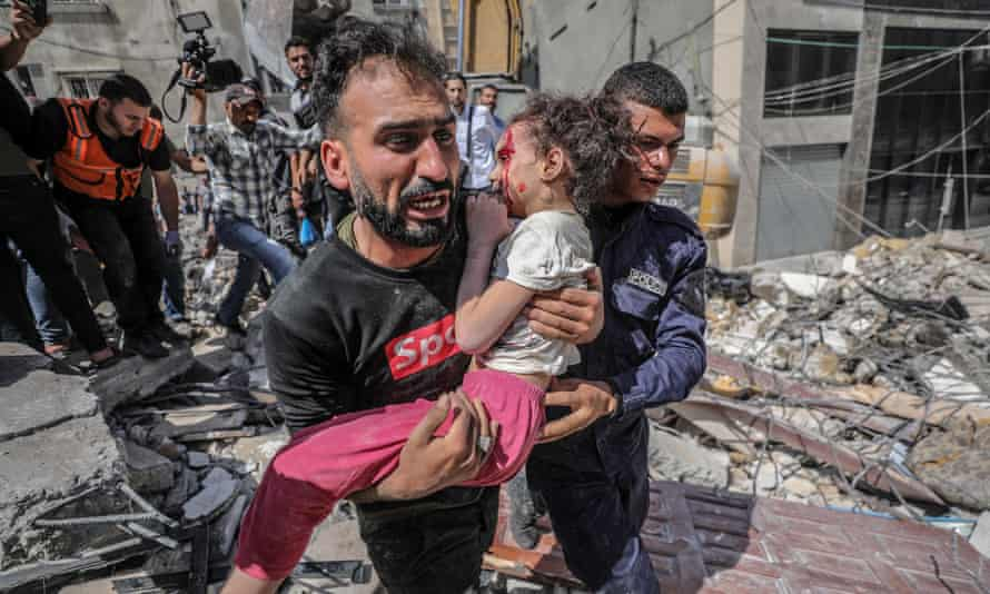 A Palestinian father carries his wounded daughter from the rubble of a destroyed house after an Israeli airstrike in Gaza City