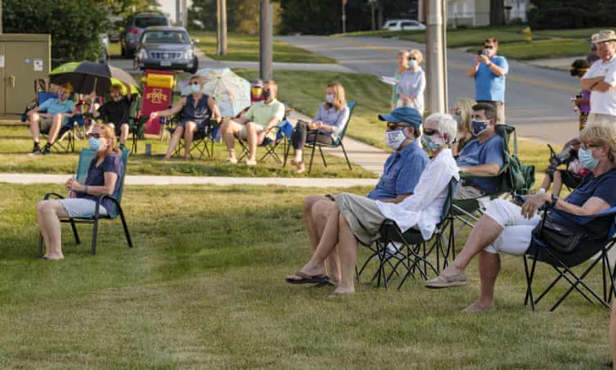 People sit on the lawn during a memorial service for the victims of Covid-19 at West Des Moines United Methodist church.
