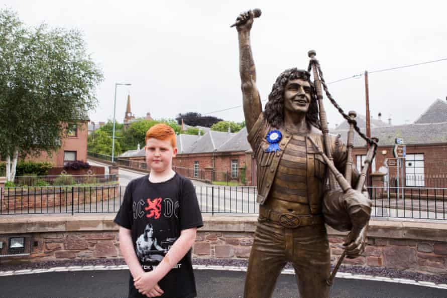 A fan next to the life-size bronze statue of AC/DC's Bon Scott in Kirriemuir.