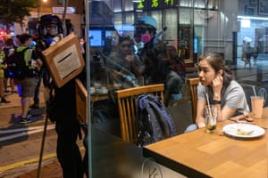 A woman sits in a restaurant as protesters gather on a street in the Wan Chai district