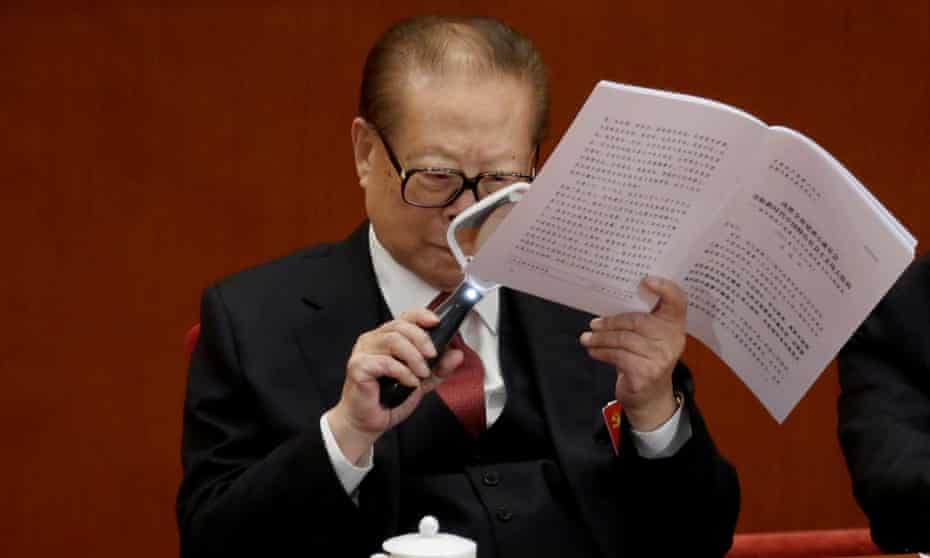 Former Chinese President Jiang Zemin uses a magnifying glass to read Chinese President Xi Jinping's report during the opening of the 19th National Congress of the Communist Party of China.