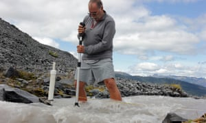 Oliver Grah measures the velocity of a stream of glacier melt stemming from Sholes Glacier