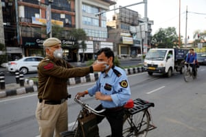 A policeman adjusts the mask of a security guard in New Delhi
