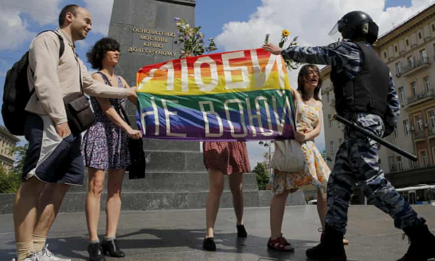 """A policeman objects to protestors holding a rainbow flag during an LGBT community rally in central Moscow, Russia, at the weekend. The sign reads, """"Love. Don't make war."""" The UN report says at least 76 countries have laws used to criminalise and harass people on the basis of their sexual orientation."""