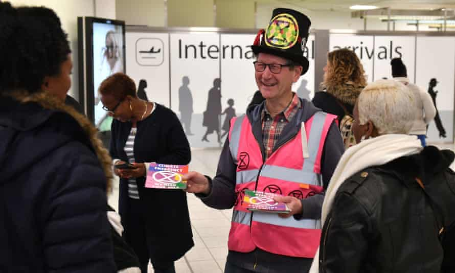 An Extinction Rebellion protester greets people arriving from international at Gatwick.