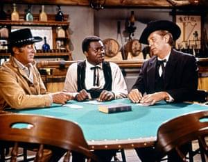 Dean Martin as Van Morgan, Yaphet Kotto as bartender Little George and Robert Mitchum as The Reverend Jonathan Rudd in 5 Card Stud, 1968