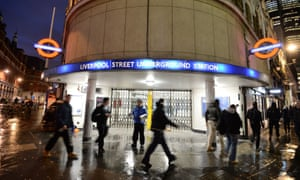 People walk past a closed Liverpool Street underground station during the tube strike