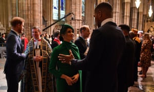 The Duchess of Sussex speaks with the British boxer Anthony Joshua as she leaves the service.