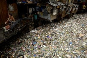 A man sits on a bike beside a rubbish-filled river in Manila